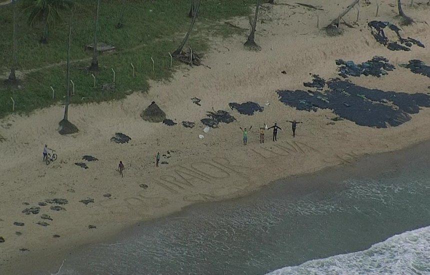 [Óleo atinge mais praias de Pernambuco e voluntários pedem ajuda por mensagem na areia]