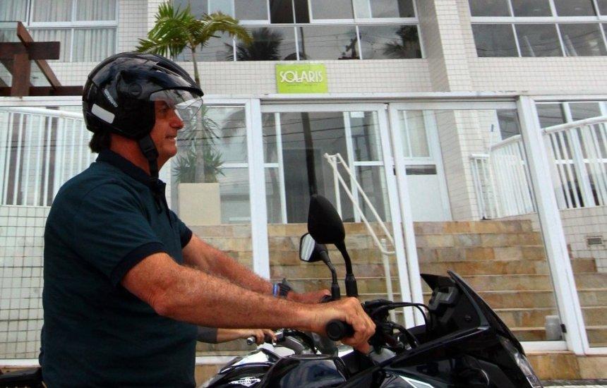 [Bolsonaro comete infração de trânsito ao andar de moto com capacete solto em Guarujá]